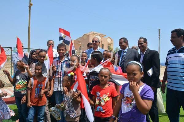 صورة تذكارية لمحافظ البحر الأحمر مع أطفال قرية الحمراوين داخل ملعب كرة القدم المقام بالنجيل الصناعى